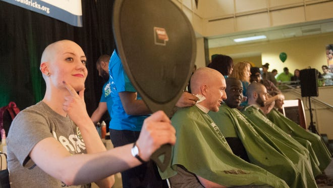 Rowan University student Sarah Poole of Blackwood takes a close look after getting her head shaved Tuesday to raise money for awareness for pediatric cancer research at Rowan University.