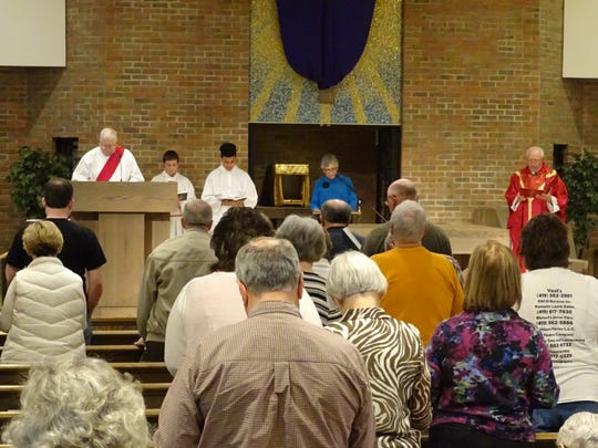 Parishioners of Holy Trinity Catholic Church read scripture during a Good Friday service.
