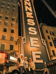 Pattison Sign Group National Sales Manager Jeff Allison, left, and Project Manager Laura Oran, right, pose with Tennessee Theatre Executive Director Becky Hancock with the 4-ton vertical sign during the sign removal.