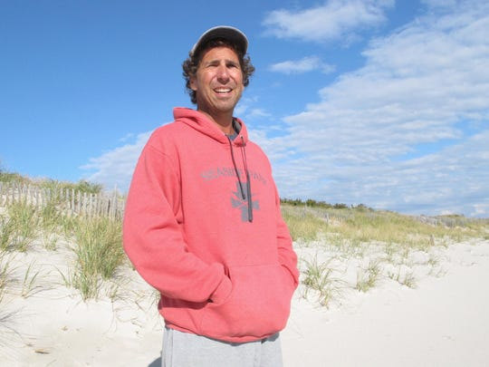 This Oct. 26, 2017 photo shows Dominick Solazzo, president of the Midway Beach Condominium Association on the beach in front of the 25-foot-tall dunes his members built and maintained over the decades in Berkeley Township, N.J. On Friday Dec. 1, 2017, a judge ruled that New Jersey can seize the beachfront land to make way for a shore protection project whose proposed dunes are smaller than what's already there. The state promised it would not shorten any dunes that are taller than those called for under its plan. (AP Photo/Wayne Parry)