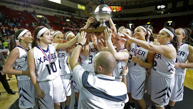 Xavier girls' basketball coach A.C. Clouthier hands the runner-up trophy to his players following a loss against Whitewater in the WIAA Division 3 state championship game March 14, 2015 at the Resch Center in Ashwaubenon.