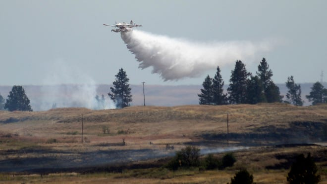 A firefighting plane drops water from Fishtrap Lake on a stubborn fire burning near the lake in Lincoln County, Sunday, July 20, 2014, near Cheney, Wash.  The fire started Saturday afternoon and spread to several thousand acres, driven by high winds.