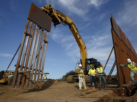 """In this Jan. 9, 2019 file photo, construction crews install new border wall sections seen from Tijuana, Mexico. Sen. Dick Durbin, D-Ill., says the Pentagon is planning to tap $1 billion in leftover funds from military pay and pensions accounts to help President Donald Trump pay for his long-sought border wall. Durbin told The Associated Press, """"it's coming out of military pay and pensions, $1 billion, that's the plan."""""""