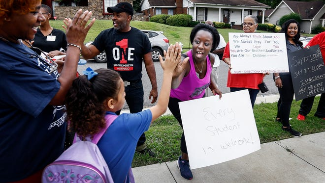 New Direction Christian Church member Luchanna Reid (middle) greets Belle Forest Community School students with high-fives as they arrive for the first day of school Monday morning.