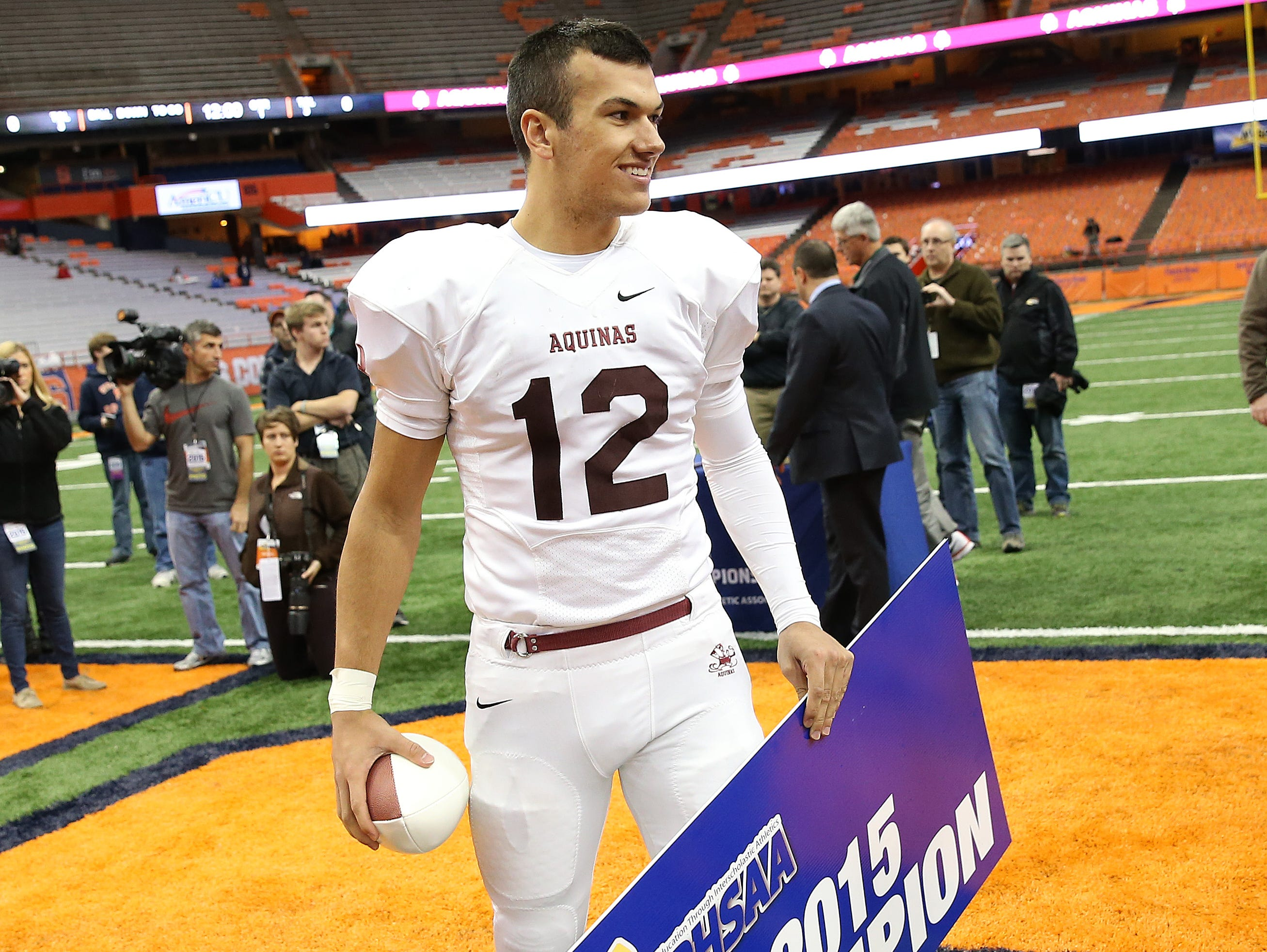 Aquinas QB Jake Zembiec holds a state championship sign and a commemorative ball after the Lil Irish won the Class AA title.