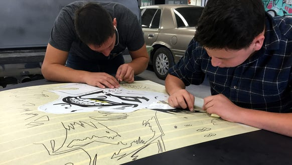 Students paint a car hood in an automotive program