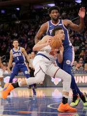 New York Knicks' Kevin Knox, bottom, tries to push past Philadelphia 76ers' Joel Embiid during the second half of the NBA basketball game, Sunday, Jan. 13, 2019, in New York. (AP Photo/Seth Wenig)