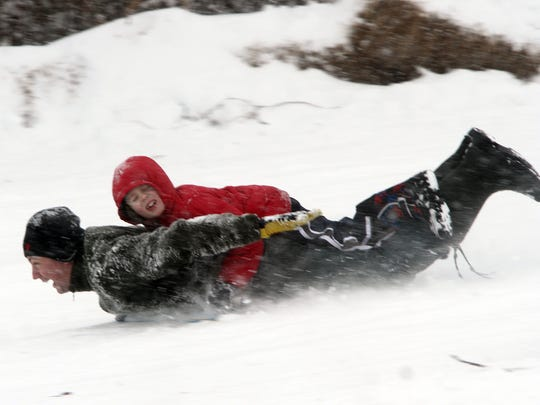 Sledders speed down a snowy hill at Donaldson Park in Highland Park in January 2015.