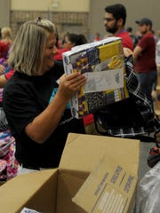 Jackie Jones places a pre-packaged school supply kit into a backpack during Project Back to School Roundup Saturday, Aug. 12, 2017 in the Ray Clymer Exhibit Hall at the MPEC.
