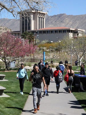 UTEP students walk through Leech Grove on campus during a class change.
