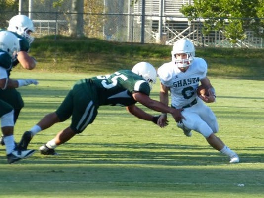 Shasta College running back Connor Silveria avoids linebacker Europa Mataia during the Green and White scrimmage Thursday.