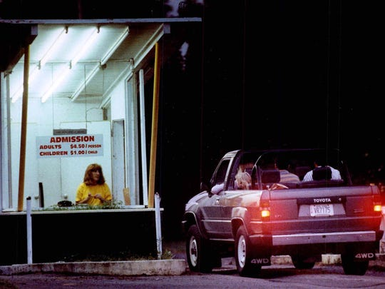 June 1991: As the sun sets, Angel Smura sells tickets at Lakeshore Drive-in, Greece.