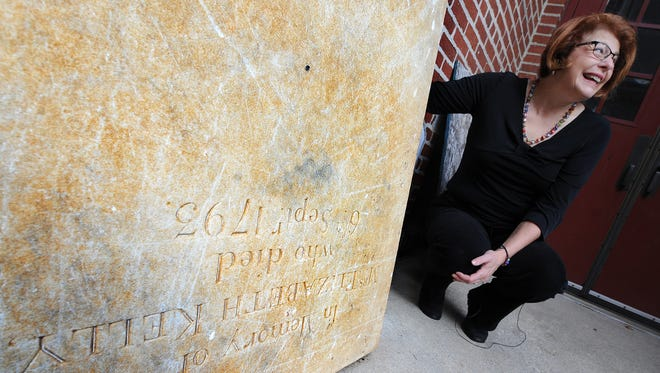 """""""This was Christmas morning. Positively."""" said Cindy Lobach, the archivist at First Presbyterian Church of York, who poses with the tombstone of Elizabeth Smith Kelly. The tombstone was discovered while a volunteer was digging up a sidewalk at the church on Monday. Kelly was the daughter of Colonel James Smith, who was a signer of the the Declaration of Independence."""