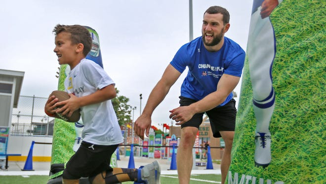 Colts quarterback Andrew Luck chases Beckett Riggs at the Riley Children?s Health Sports Legends Experience, part of the Change the Play program. The exhibit is open through November. Indianapolis Colts quarterback Andrew Luck plays with kids, including Beckett Riggs, at the Sports Legends Experience at the Children's Museum of Indianapolis, Friday, May 18, 2018.  The activities were part of the Change the Play program.  Luck and Riley Children's Health put on the Change the Play program to help teach kids to make good decisions about nutrition and exercise.