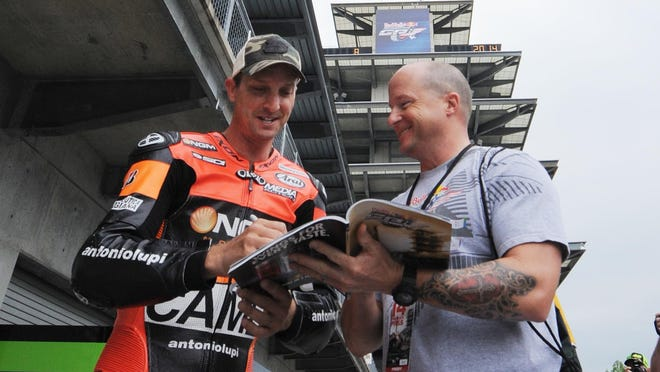 Colin Edwards signs an autograph for Mark Wicklein of Indianapolis before  practice for the Grand Prix of Indianapolis MotoGP race, Friday Aug.8, 2014 at The Indianapolis Motor Speedway.