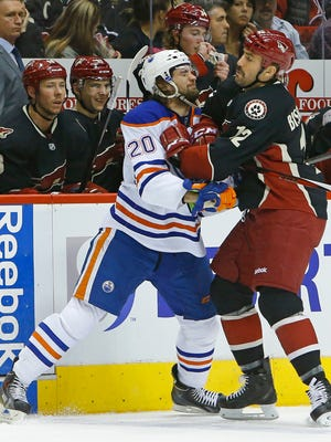 Oilers left wing Luke Gazdic (20) takes a hit from Coyotes left wing Paul Bissonnette last season. Bissonnette is a free agent.