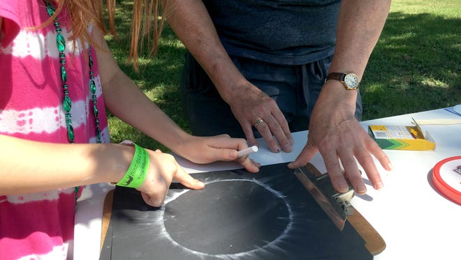 A girl smudges chalk on construction paper to simulate how the sun will look when there is a solar eclipse on Aug. 21. The booth was part of a Girls Scouts Block Party in Waite Park Saturday, July 22, 2017.