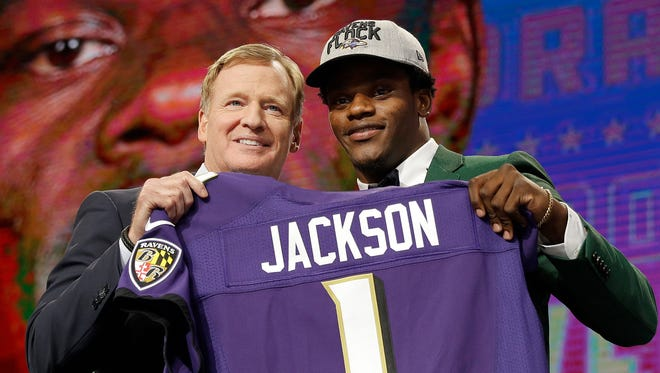 Commissioner Roger Goodell, left, presents Louisville's Lamar Jackson with his Baltimore Ravens jersey during the first round of the NFL football draft, Thursday, April 26, 2018, in Arlington, Texas.