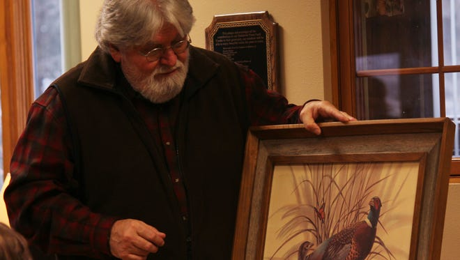 Paul Helbach displays the artwork his family is donating to the Portage County Health Care Center on Tuesday, Feb. 2.