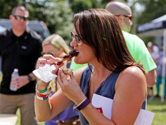 Tara Greene, of Staunton, eats a pork barbeque rib