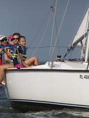 From front to back, Cypress Lake Middle School students, Jenny Nichols, Reece Hall and Marian Hanlon, all 13, take part in a free one week sailing school put on by Steve and Doris Colgate's Offshore Sailing School. Instructing them is David McMullen, back left.