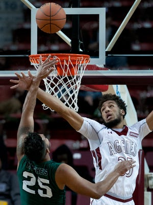 New Mexico State's Johnny McCants tries to block the shot of Eastern New Mexico's Andre Hughes Tuesday night at the Pan American Center.