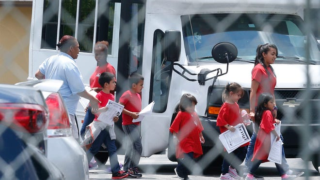 In this June 21, 2018, photo, migrant children walk off a bus at the Catholic Charities' Msgr. Bryan Walsh Children's Village in Cutler Bay, Fla. Congresswoman Debbie Wasserman Schultz said Monday, June 25, that children who range in age from newborns to 5 years old are being sheltered at this facility and His House Children's Home in Miami Gardens.