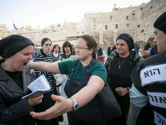 "FILE - In this June 9, 2013 file photo, an Israeli member of the ""Woman of the Wall"" organization, right, tries to hug an ultra-Orthodox woman as they pray at the Western Wall, the holiest site where Jews can pray, in Jerusalem's old city. Israeli police say dozens of ultra-Orthodox Jews attacked buses bearing photos of women worshipping like men do. The advertisements on the buses were by Women of the Wall, a group that seeks to promote gender equality at Jerusalem's Western Wall, the holiest site where Jews can pray. The ads showed women and girls holding Torah scrolls, an act which many Orthodox Jews say is reserved for men. (AP Photo/Michal Fattal,File) ISRAEL OUT"