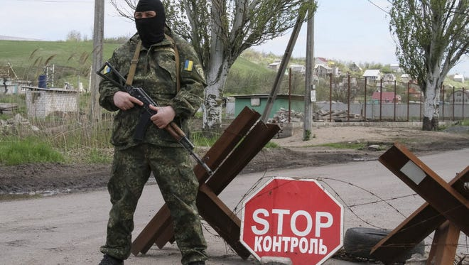 A masked Ukrainian serviceman stands guard at a checkpoint in the village of Vinogradnoye, near the eastern city of Mariupol, Ukraine, on May 5.