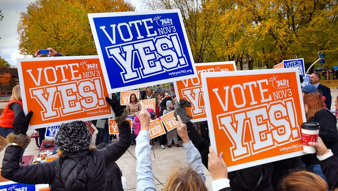 Supporters hold signs in support of the coming District 742 referendum during a rally Saturday at Lake George in St. Cloud.