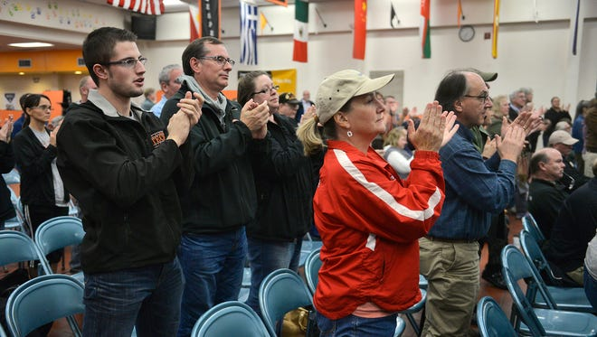Attendees rise to their feet in the St. Cloud Tech cafeteria for a standing ovation Tuesday night after Friends of Clark Field organizer Ruth Kaczor read a plea to consider other options for an early childhood center and district offices instead of building on Clark Field.