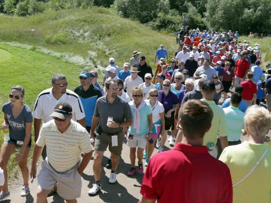 Hundreds of golf fans walk near the 18th hole at Whistling