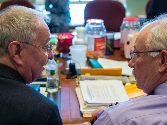 Rep. Albert Pearce, R-Richford (left), discusses details of the state budget with fellow appropriations committee member Rep. Robert Helm, R-Castleton, at the Statehouse in Montpelier on Thursday.