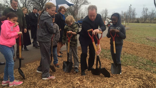 Mayor Greg Fischer and Medora Elementary School students finishing a tree planting on Friday.
