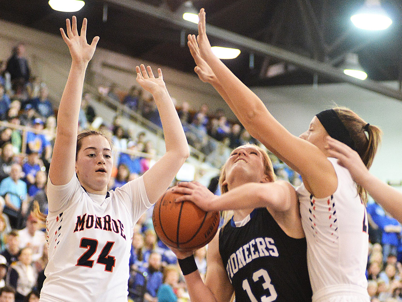 Western Mennonite's Madison Hull shoots the ball guarded by Monroe's Emily Stahl (24) and Kyndal Martin.