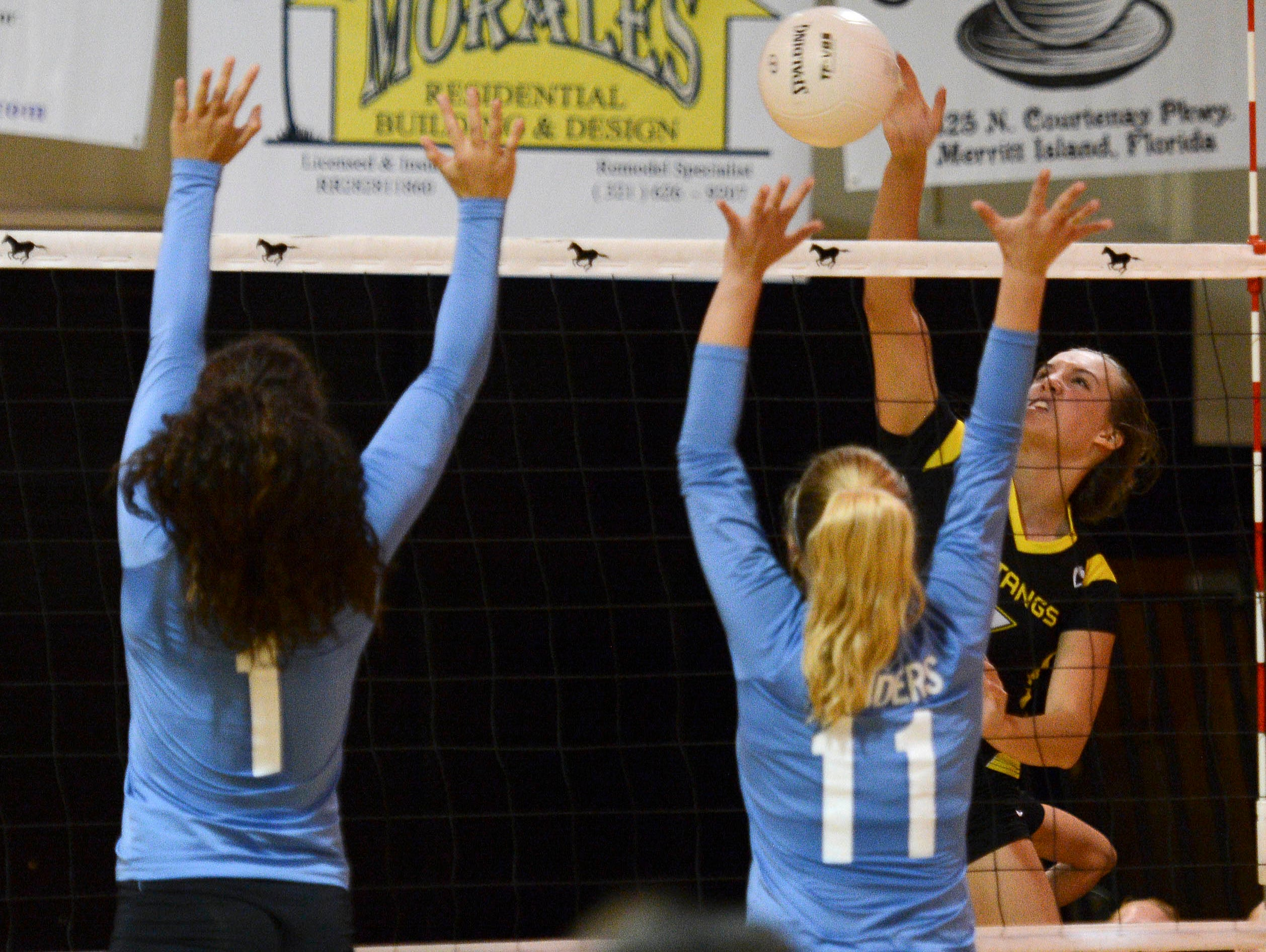 Merritt Island's Alyssa Zwolensky spikes over the block of Taylor Miles (1) and Katy Seymour of Rockledge during Thursday's Class 5A District 14 championship match.