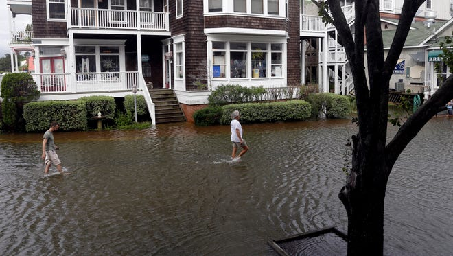 People walk along a flooded street near the waterfront in Manteo, N.C., Friday, July 4, 2014, after Hurricane Arthur passed through the area leaving some roads underwater.