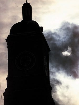 A partial eclipse of the sun is visible next to a sillhouette of the Wells Fargo Bank tower in downtown Davenport, Iowa, on Dec. 25, 2000.