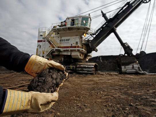 A mine worker holds a handful of tar sands oil in 2006