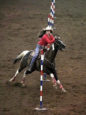Kailey Schmidt of Cottage Grove competes in the pole bending event during the Tennessee High School Rodeo at the Williamson County Ag Expo Park in Franklin on Saturday, April 8, 2017. About 100 high school students from Tenn., Miss, and Ala. competed in the two day rodeo.