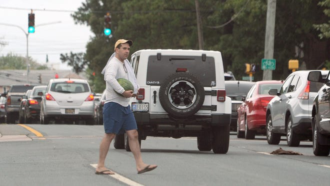 A man crosses Route 1 after making a quick stop at a fruit stand in Dewey Beach. Some new, flashing signs have appeared along coastal Del 1 letting motorists and pedestrians know they should follow the laws.