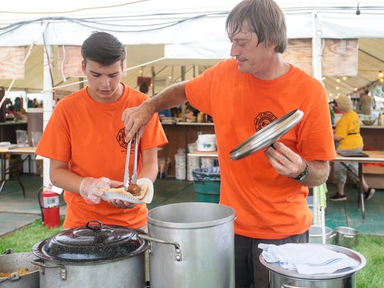 Chris Goldberg, 15, of Somerset prepares a kielbasa sandwich with help from Istvan Hajbunemeth at the Middlebush Fire Department booth at the Somerset County 4H Fair in North Branch Park on August 10, 2016.