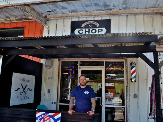 Danny Rainey, co-owner of The Chop Barbershop, stands in front of the shop's new location in Railroad Square