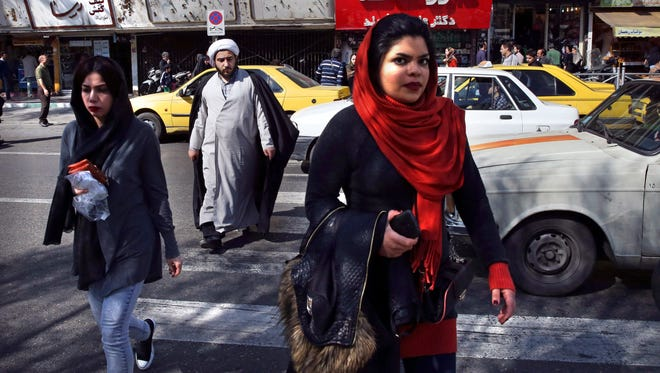Pedestrians cross a square on Feb. 27, 2016, a day after parliamentary elections in Iran.