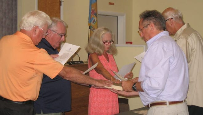 Returning Fenwick Island town council members were sworn in simultaneously with the same Bible on Aug. 15. Pictured are council members Roy Williams (left), Mayor Gene Langan, Julie Lee, Secretary Bernie Merritt and Vice Mayor Richard Mais.