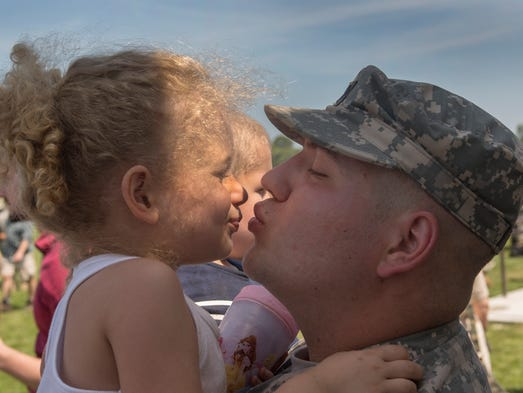 Specialist Ryan Kreger of Manalapan plants a kiss on the face of this four year old daughter Isabella after ceremony. Salute To Troops 1-114th Infrantry  deployment in Operation Enduring Freedom on June 18, 2014 at Joint Base McGuire-Dix-Lakehurst.   Photo by Peter Ackerman