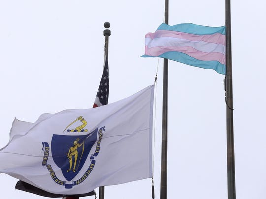 A flag representing the transgender community, foreground, flies next to the Massachusetts state flag and a U.S. flag in front of Boston City Hall. Democratic Boston Mayor Marty Walsh, a supporter of transgender rights, said the flag will continue to fly until everyone is equal under the law in Massachusetts.