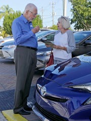 In this Friday, Feb. 10, 2017, photo, Earl Stewart, owner of a Toyota dealership, talks to a customer at his business in North Palm Beach, Fla.