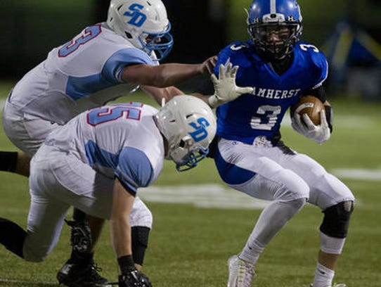 Amherst's Josh Cisewski, right, carries the ball against