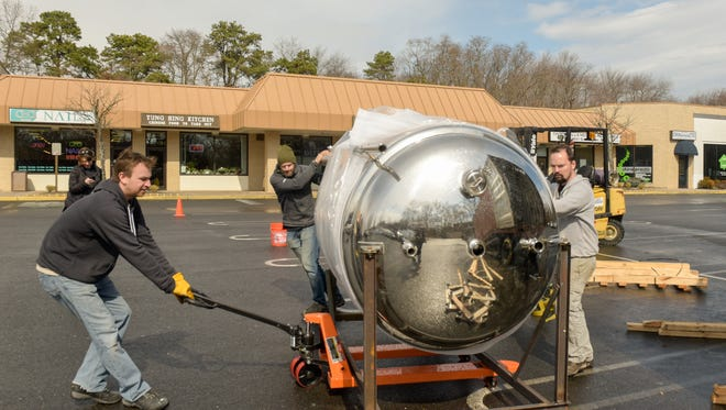 Co-owners Mike Skudera (left), Peter Artherholt (center) and Chris Hanigan move a 15-barrel beer fermenter for Jughandle Brewing Co. in Tinton Falls.
